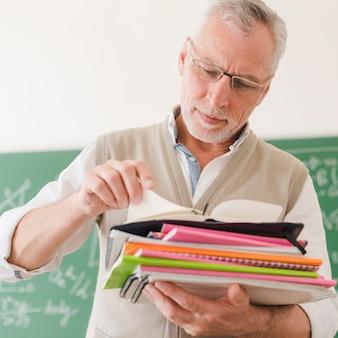 Älterer lehrer, der notizblöcke im klassenzimmer überprüft