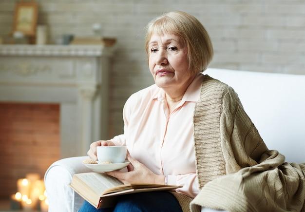 Älterer leser im wohnzimmer