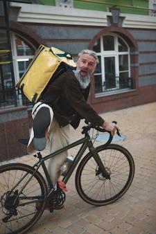 Älterer lieferbote mit dem fahrrad, das lustiges gesicht genießt, das arbeitet