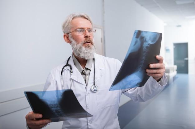 Älterer männlicher arzt, der röntgenaufnahmen im krankenhaus untersucht