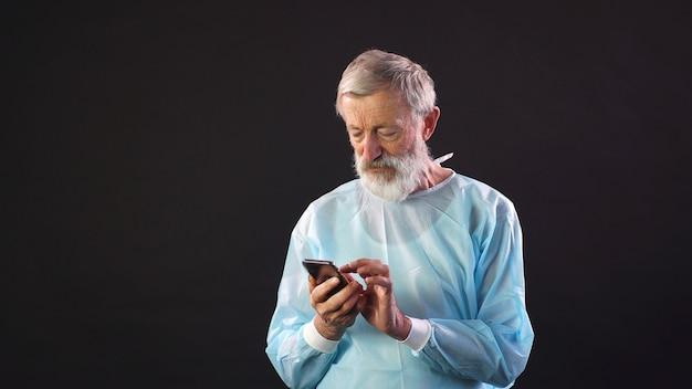 Älterer männlicher arzt in einem medizinischen anzug mit einem telefon in den händen auf einem isolierten dunklen raum.