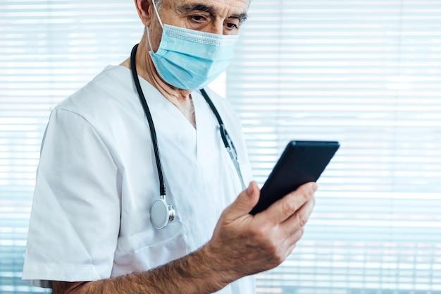 Älterer männlicher arzt - krankenschwester, die gesichtsmaske trägt und handy neben einem krankenhausfenster betrachtet. covid-19 und medizinkonzept