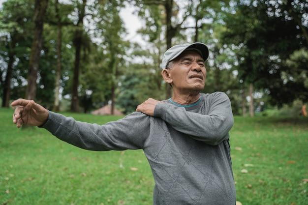 Älterer männlicher asiat, der schmerzende schulter und schmerzen an seinem gelenk hat