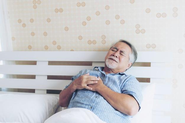 Älterer männlicher asiat, der zu hause unter den schlimmen schmerz in seinem kastenherzangriff leidet