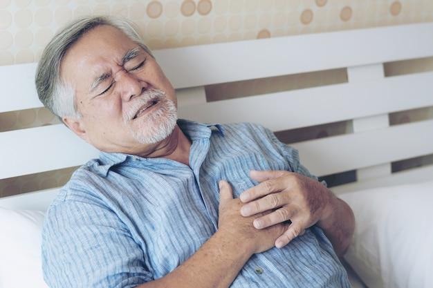 Älterer männlicher asiat, der zu hause unter schlechten schmerz in seinem kastenherzanfall - ältere herzkrankheit leidet