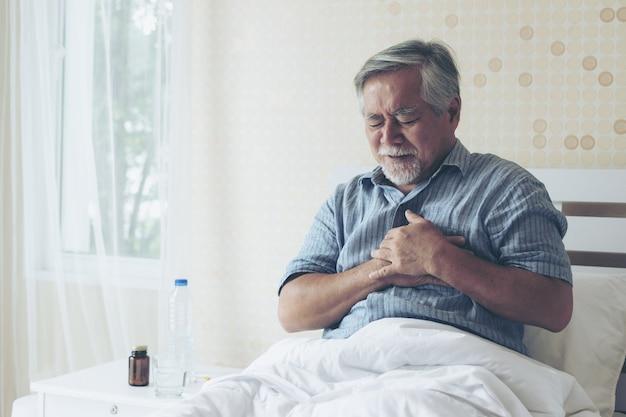 Älterer männlicher asiat, der zu hause unter schlechten schmerz in seinem kastenherzinfarkt - älteres herz leidet
