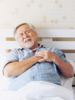 Älterer männlicher asiate, älterer mann, alter mann, der unter starken schmerzen in seinem brustherzinfarkt im schlafzimmer zu hause leidet - senior-herzkrankheit