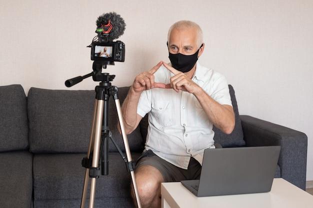 Älterer männlicher blogger in maske zu hause, der video zu hause aufzeichnet, blogging, videoblog und personenkonzept