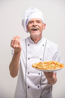 Älterer männlicher hauptkoch in der uniform, die pizza hält.