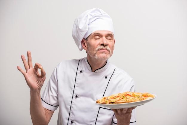 Älterer männlicher hauptkoch in der uniform okayzeichen gestikulierend.