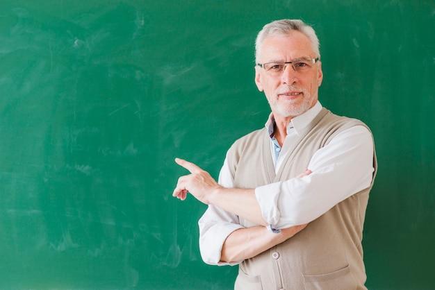 Älterer männlicher lehrer, der auf grüne tafel zeigt