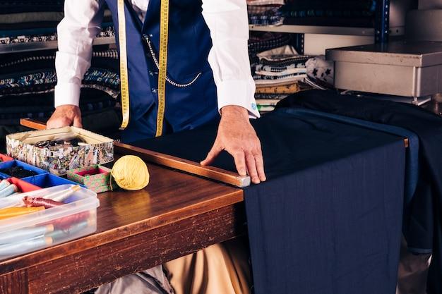 Älterer männlicher modedesigner, der maß des gewebes auf holztisch nimmt