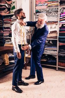 Älterer männlicher modedesigner, der maße seines kunden im shop nimmt