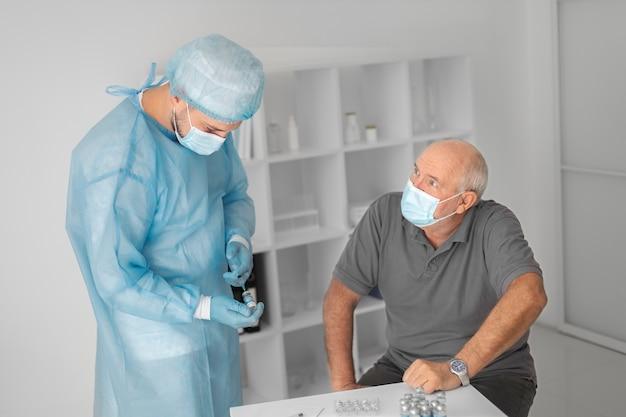 Älterer männlicher patient, der gegen coronavirus geimpft wird
