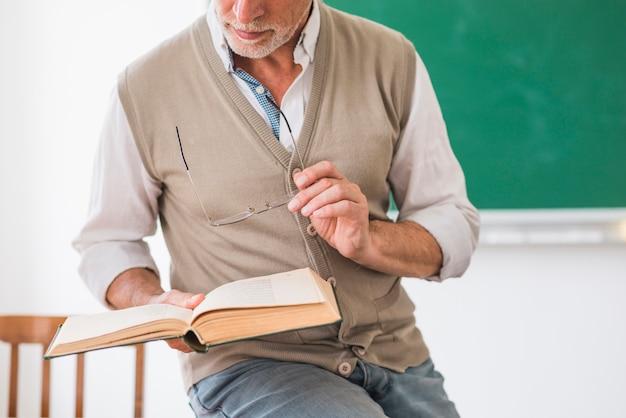 Älterer männlicher professor, der buch und gläser im klassenzimmer hält