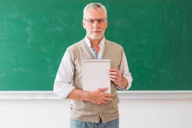 Älterer männlicher professor, der das notizbuch steht gegen tafel hält