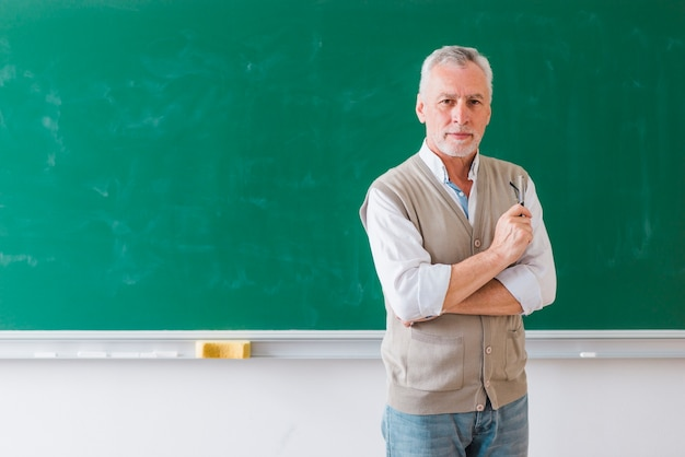 Älterer männlicher professor, der gegen grüne tafel steht
