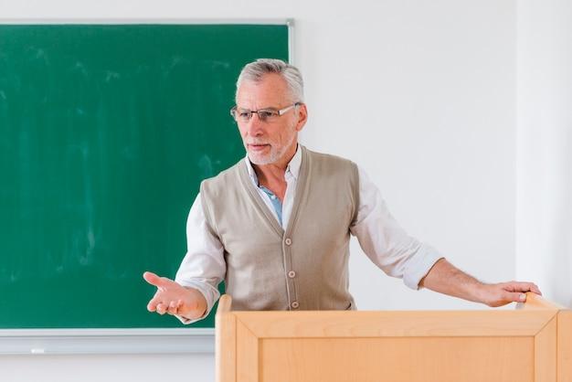 Älterer männlicher professor, der lektion nahe tafel erklärt