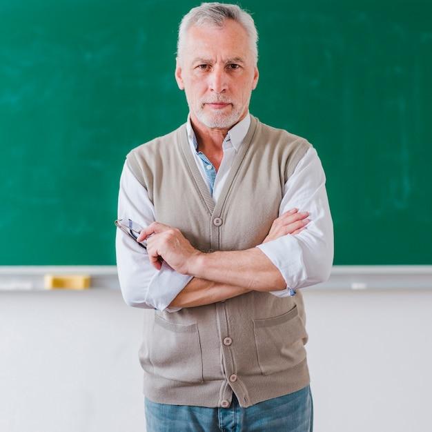 Älterer männlicher professor mit den armen kreuzte stellung gegen tafel