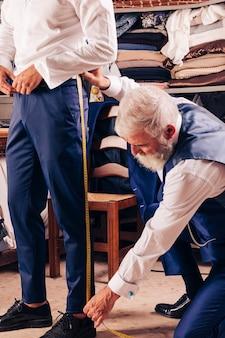 Älterer männlicher schneider, der das bein des kunden im shop misst