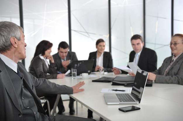 Älterer männlicher sprecher, der eine darstellung bei einem geschäftstreffen im büro gibt