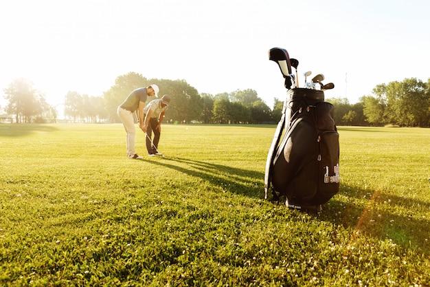 Älterer männlicher trainer, der jungen sportler lehrt, wie man golf spielt