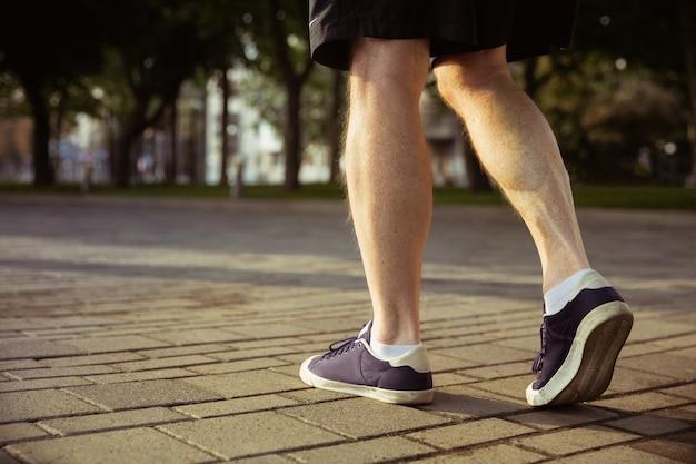 Älterer mann als läufer an der stadtstraße. nahaufnahme schuss von beinen in turnschuhen