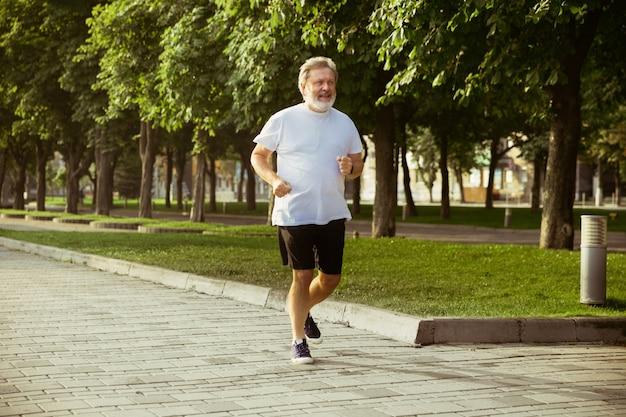 Älterer mann als läufer mit armbinde oder fitness-tracker an der stadtstraße