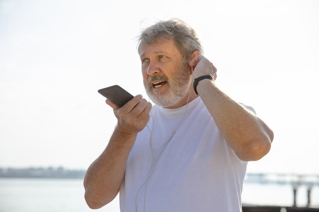 Älterer mann als läufer mit fitness-tracker am flussufer