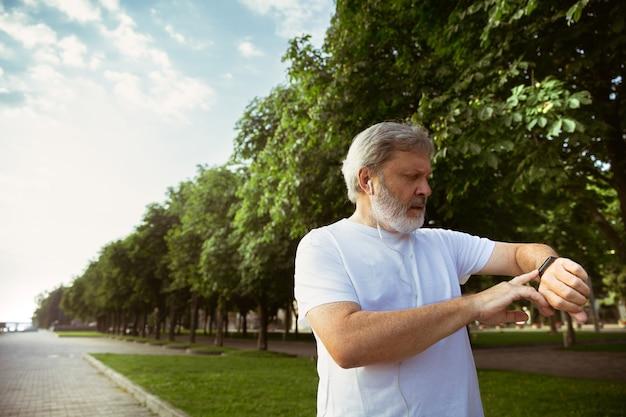 Älterer mann als läufer mit fitness-tracker an der stadtstraße