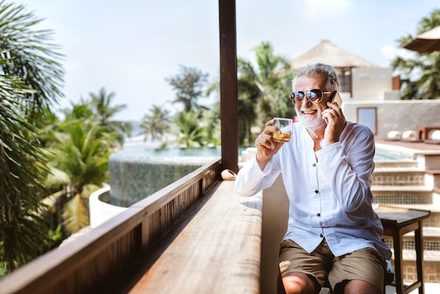 Älterer mann am telefon, das etwas trinkt