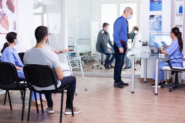 Älterer mann an der krankenhausrezeption, der gesichtsmaske trägt und mit einer krankenschwester nimmt, während er auf die coronavirus-untersuchung wartet