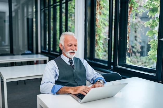 Älterer mann arbeitet an laptop.