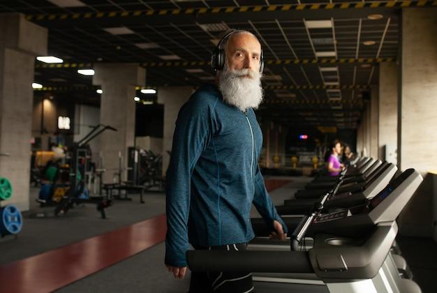 Älterer mann auf laufender maschine im fitnessstudio