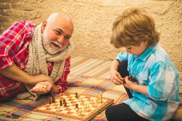Älterer mann aus der kindheit, der seinem enkel beibringt, schach zu spielen, kind spielt schach, großvater und enkel ...