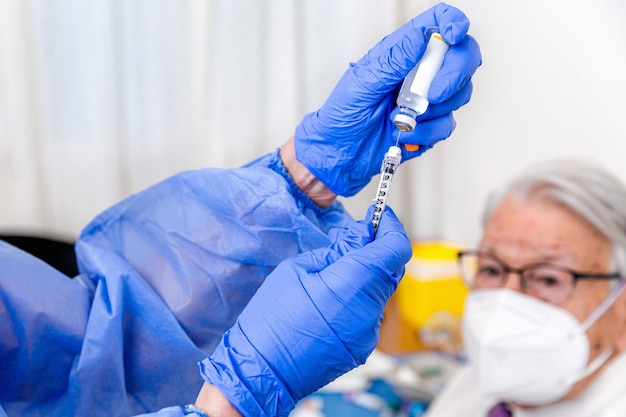 Älterer mann beobachtet, wie krankenschwester in schutzanzug und hygienehandschuhen seinen coronavirus-impfstoff vorbereitet