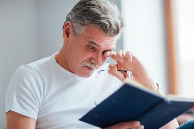 Älterer mann bildet sich weiter und liest ein buch, entspannt auf seiner couch in seinem wohnzimmer.