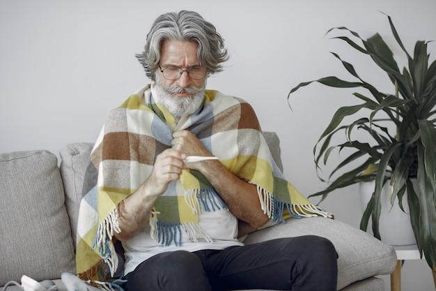 Älterer mann, der allein auf sofa sitzt. kranker mann mit plaid bedeckt. grangfather mit thermometer.