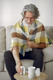 Älterer mann, der allein auf sofa sitzt. kranker mann mit plaid bedeckt. großvater mit einer tasse tee.