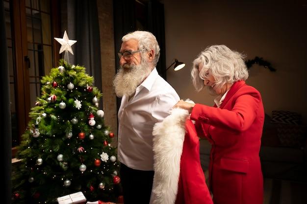 Älterer mann, der als weihnachtsmann sich kleidet