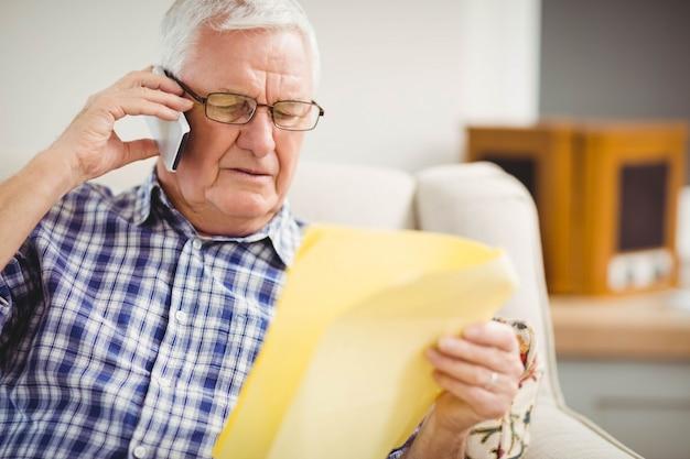 Älterer mann, der am handy beim betrachten eines dokuments im wohnzimmer spricht