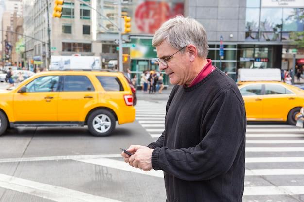 Älterer mann, der am handy in new york schreibt