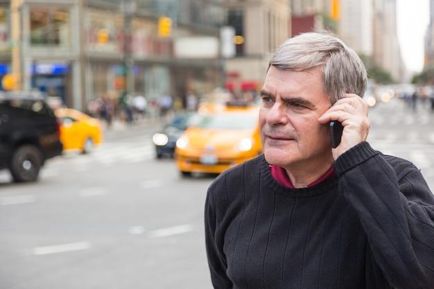 Älterer mann, der am handy in new york spricht