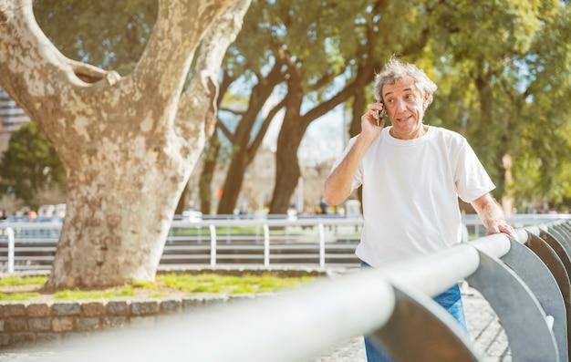 Älterer mann, der am handy steht nahe dem geländer im park spricht