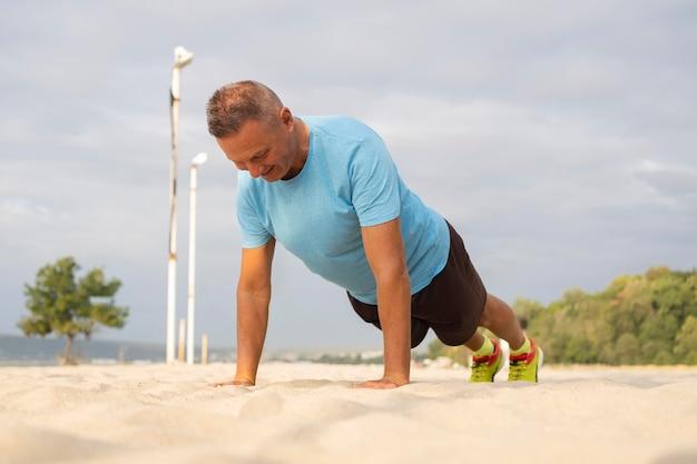 Älterer mann, der am strand arbeitet