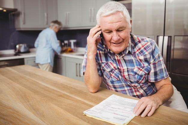Älterer mann, der am telefon und an frau zu hause arbeiten in der küche spricht