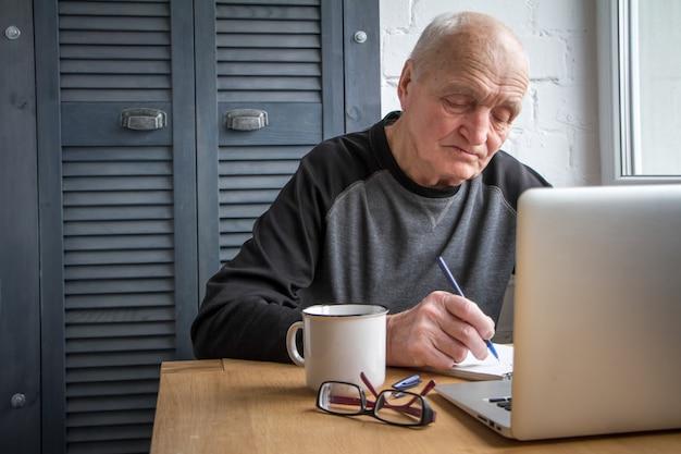 Älterer mann, der an dem laptop, schirm betrachtend arbeitet