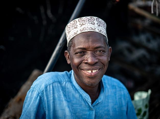 Älterer mann, der an der küste sitzt und nett mit dem hohen qualitätsfoto des hutes lächelt