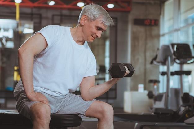 Älterer mann, der an der turnhalle ausarbeitet