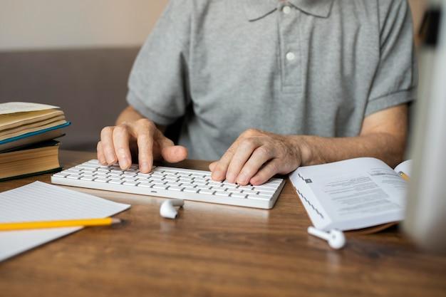 Älterer mann, der an einem online-kurs auf seinem computer teilnimmt